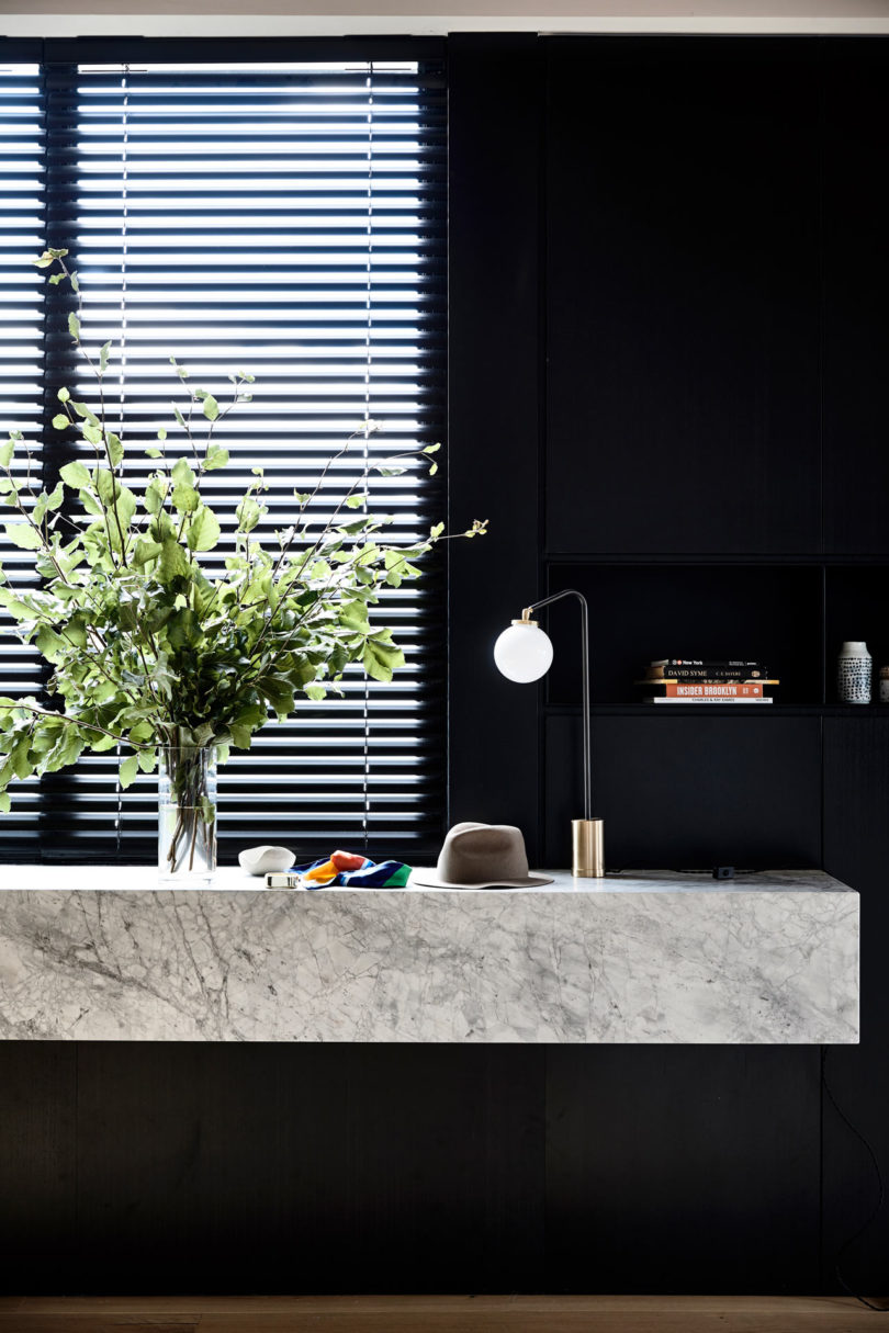 The dark entryway shows off a floating stone vanity with lamps and lights