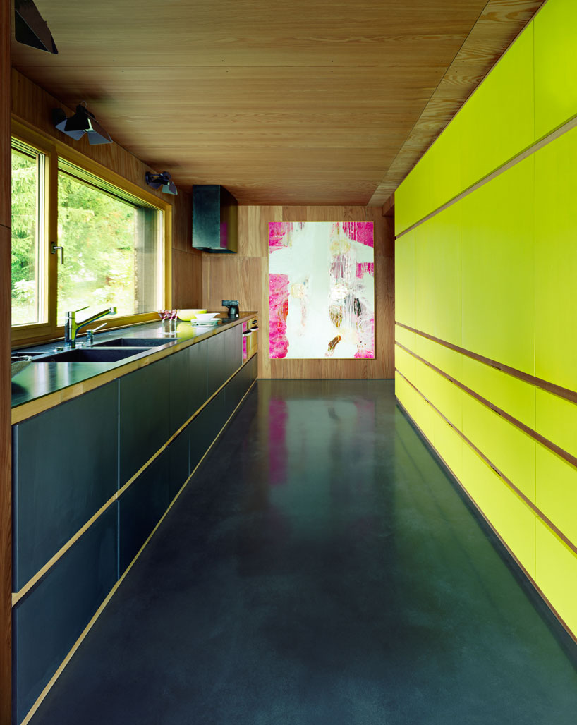 The kitchen is done in black with a contrasting neon yellow wall and a bold artwork