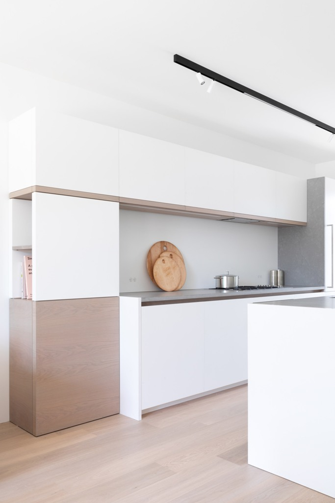 The kitchen is minimalist, in white and beige, with sleek cabinets and a concrete backsplash and countertops