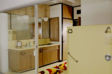 07 The master bathroom is very eye-catchy, with yellow tuiles and brown wooden furniture plus storage items