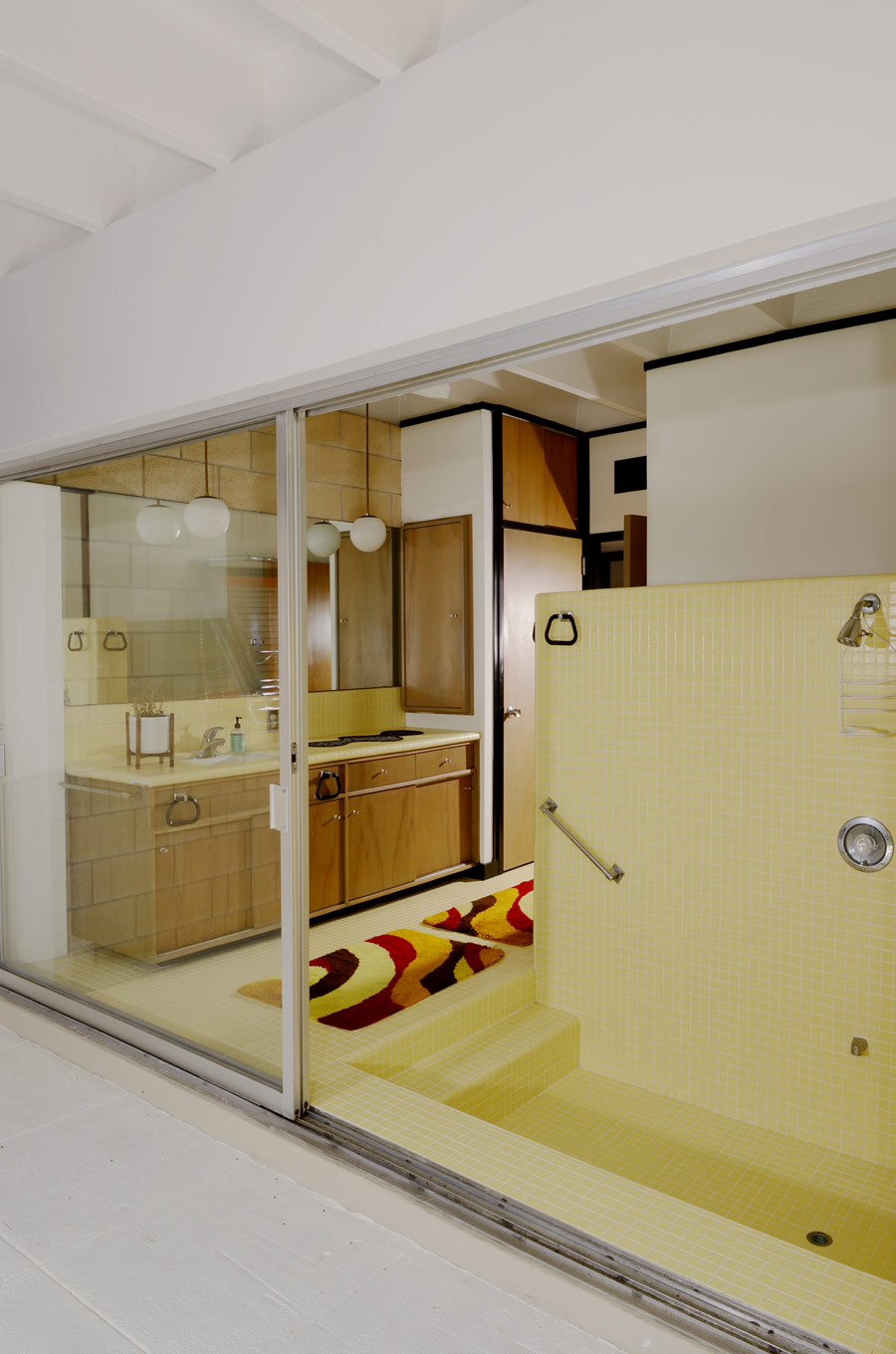 The master bathroom is very eye catchy, with yellow tuiles and brown wooden furniture plus storage items