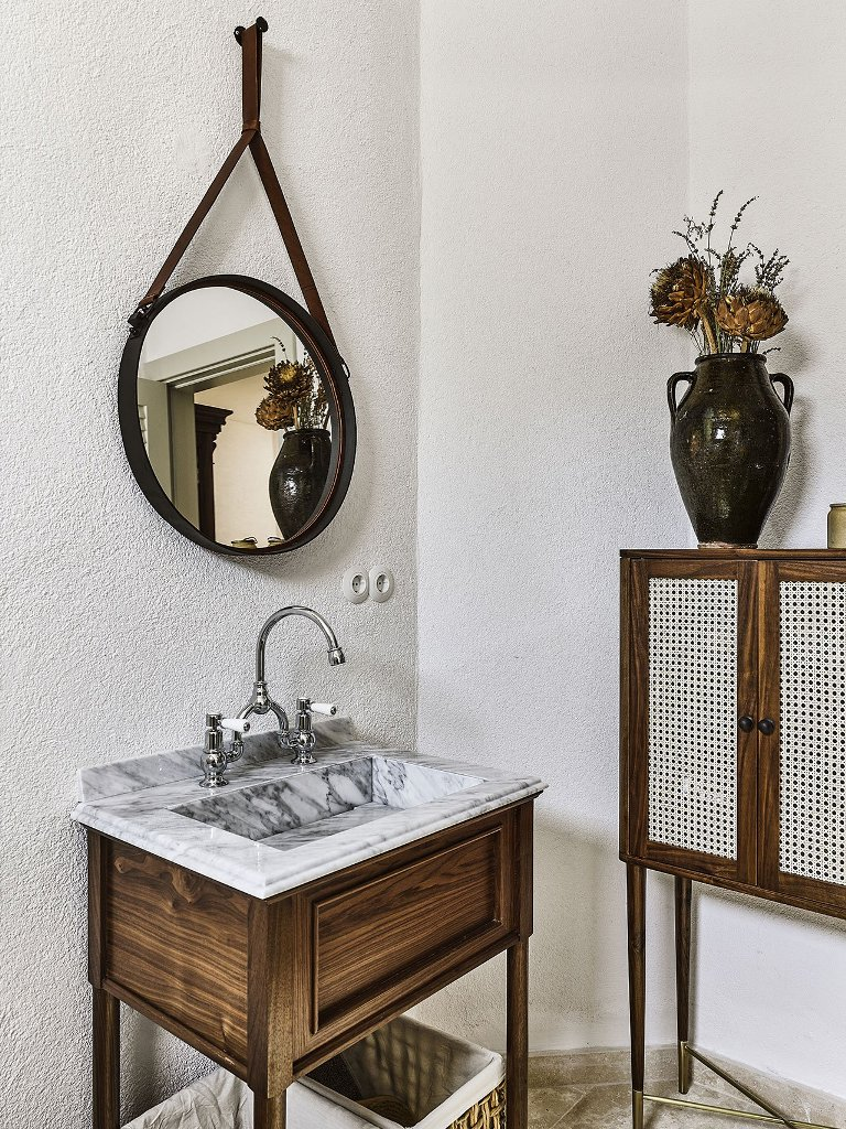 The master bathroom shows off a marble sink, wood and a cool colonial-style cabinet