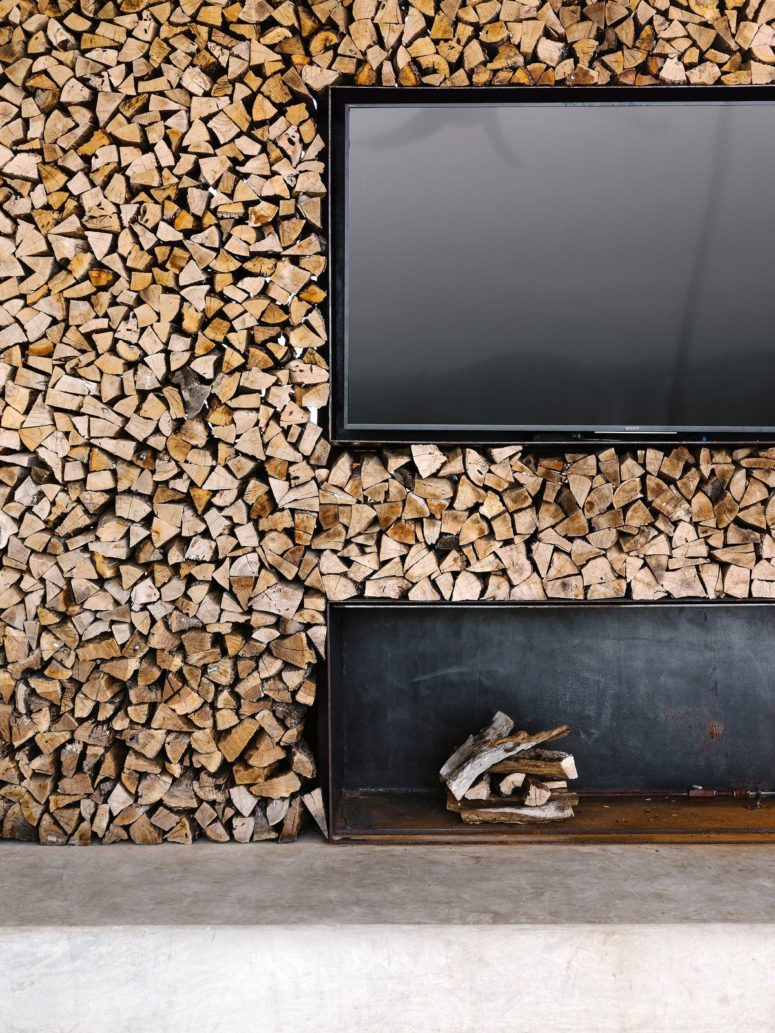 There's a whole firewood wall with a TV and a niche for a rustic feel