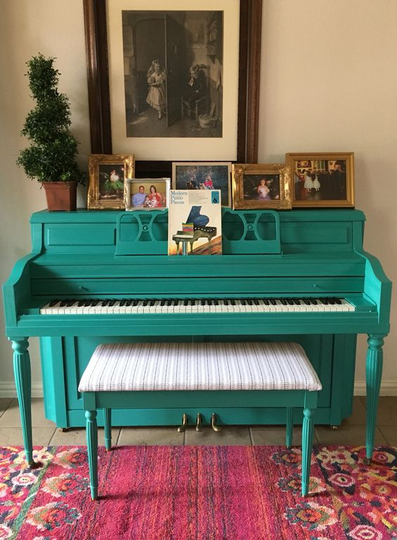 a bold turquoise piano and a matching stool with upholstery, family photos on display