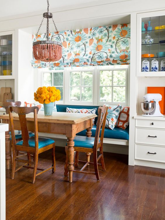 a colorful kitchen with a bold and bright eating space with a rustic dining set and an upholstered banquette