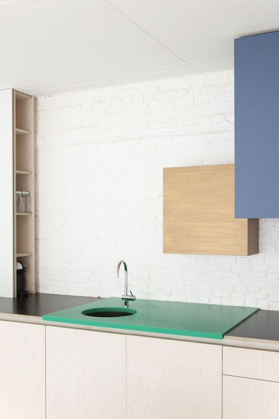a plywood and a muted blue sleek cabinet on the wall and an emerald sink countertop for a color block effect