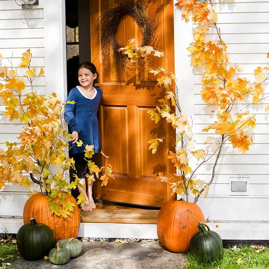 fall pumpkins with tall fall branches with leaves that imitate real trees on the porch