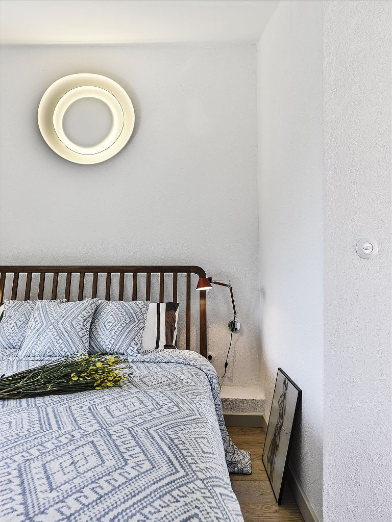 A guest bedroom is done with a large bed and a catchy wall lamp