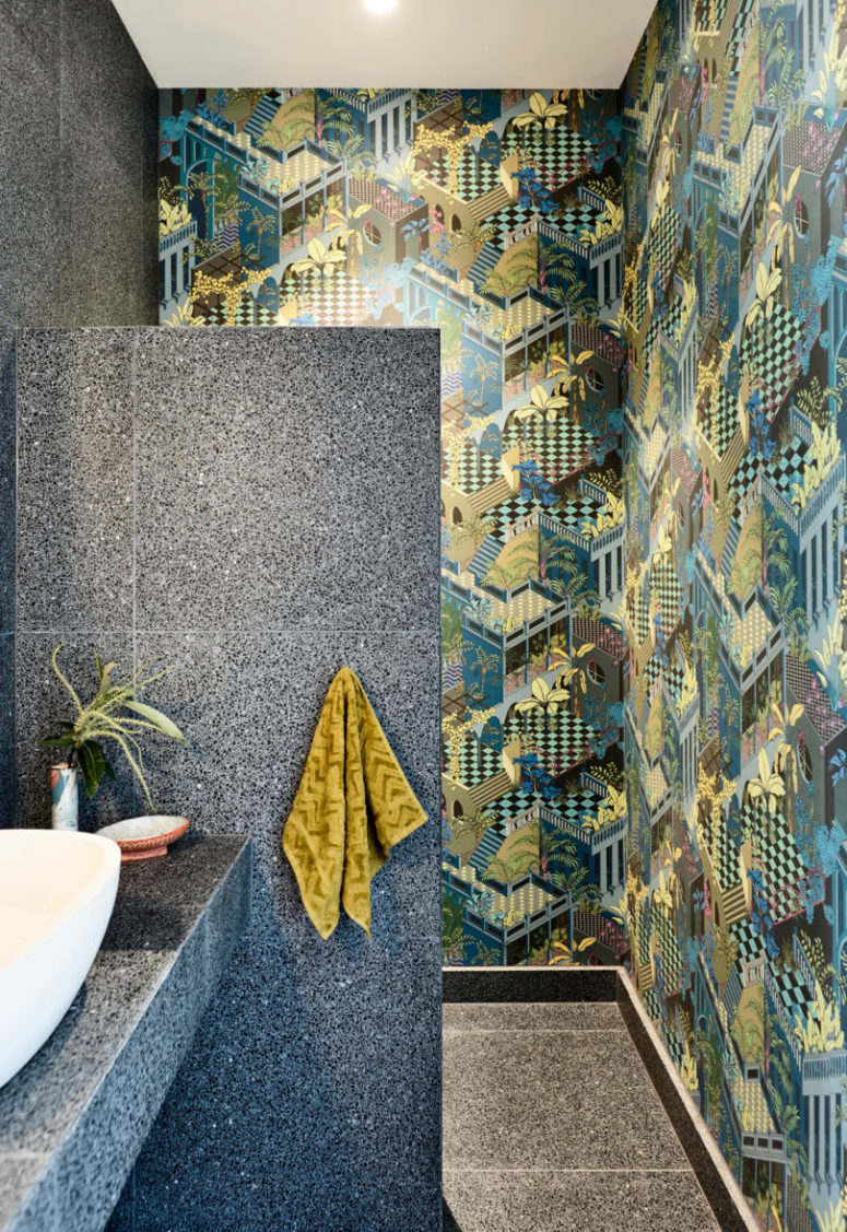 A powder room is done with extra bold printed wallpaper and stone-inspired tiles