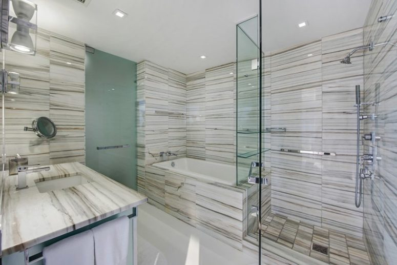 One of the bathrooms clad with marble completely and with a use of glass and metal