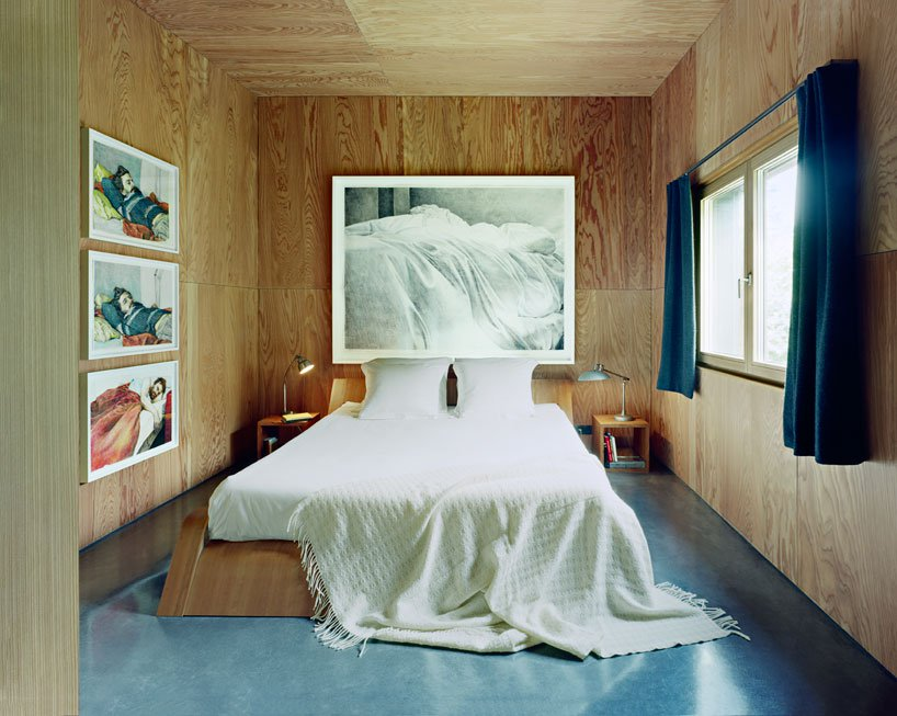 The master bedroom is all clad with plywood, and the furniture is made of it, too, a series of artworks and a cool view make it special