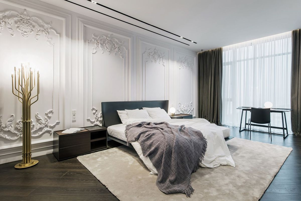 The master bedroom is done with moldings, modern furniture and touches of brass for a glam feel