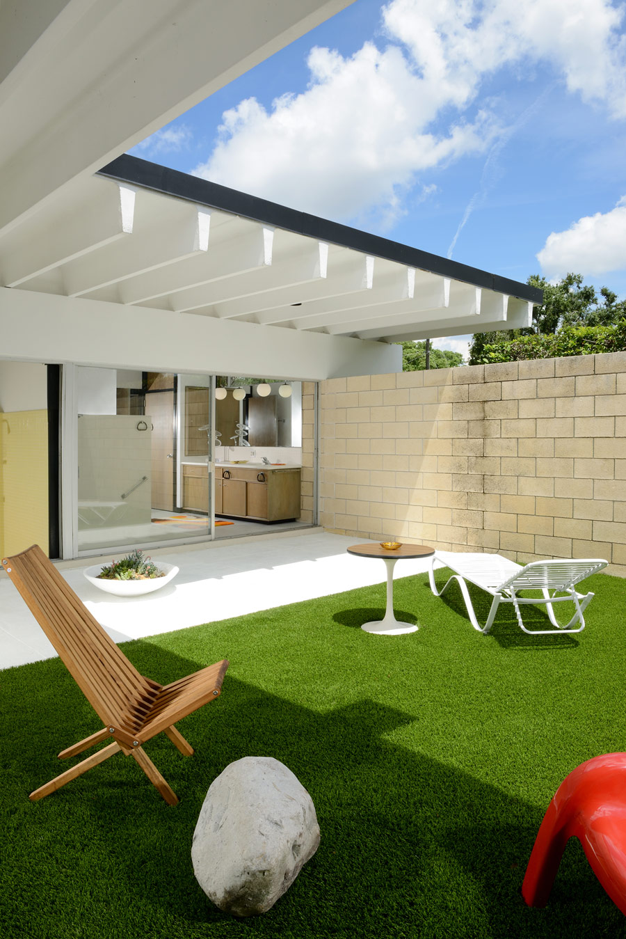 The outdoor space includes some loungers, sitting zones and a perfect lawn