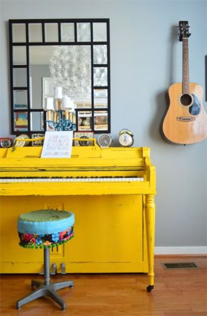 a bright yellow piano and a colorful stool, a framed mirror and a display of vintage clocks on the piano