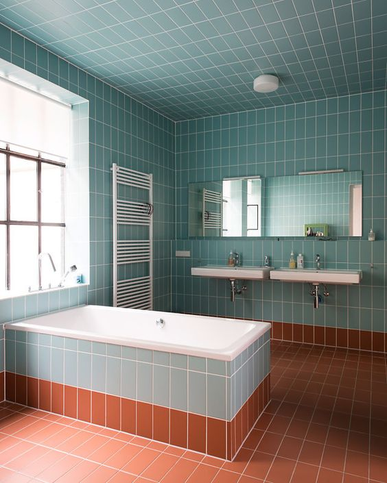a light blue and rust bathroom fulled clad with tiles and diluted with whites here and there