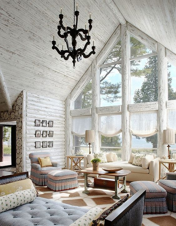 a rustic space with an attic roof is highlighted with whitewashed wood walls and ceiling plus frames of the windows