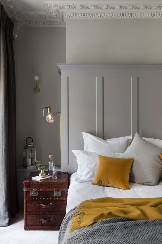 make your grey bedroom more interesting with mustard pillows and blankets and a mahogany nightstand
