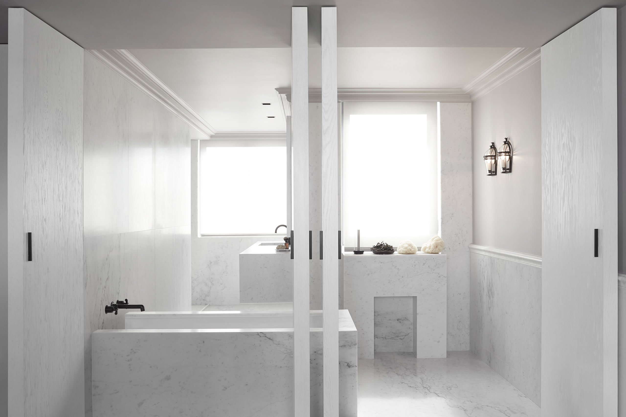 The bathroom is clad with white marble and is highlighted with black fixtures