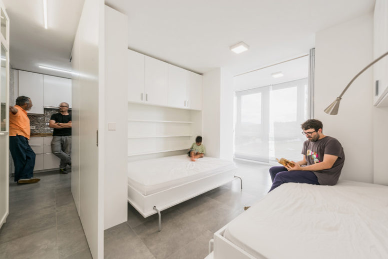 The bedroom area features two fold-down wall beds which frame the large windows
