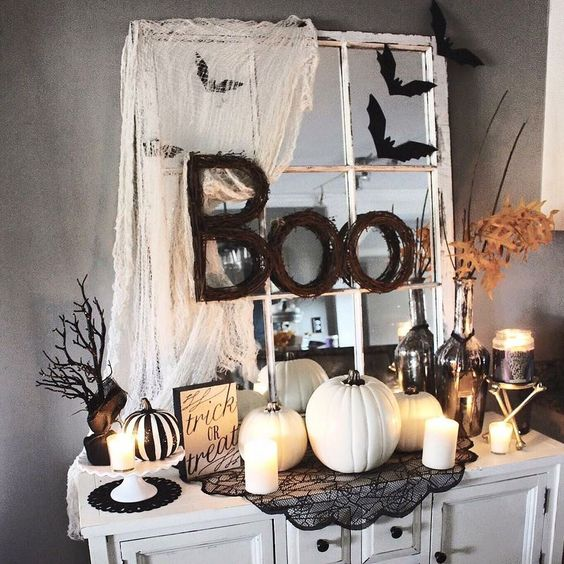 a Halloween console in black and white, with fake pumpkins, candles, lace and twig letters plus a window frame