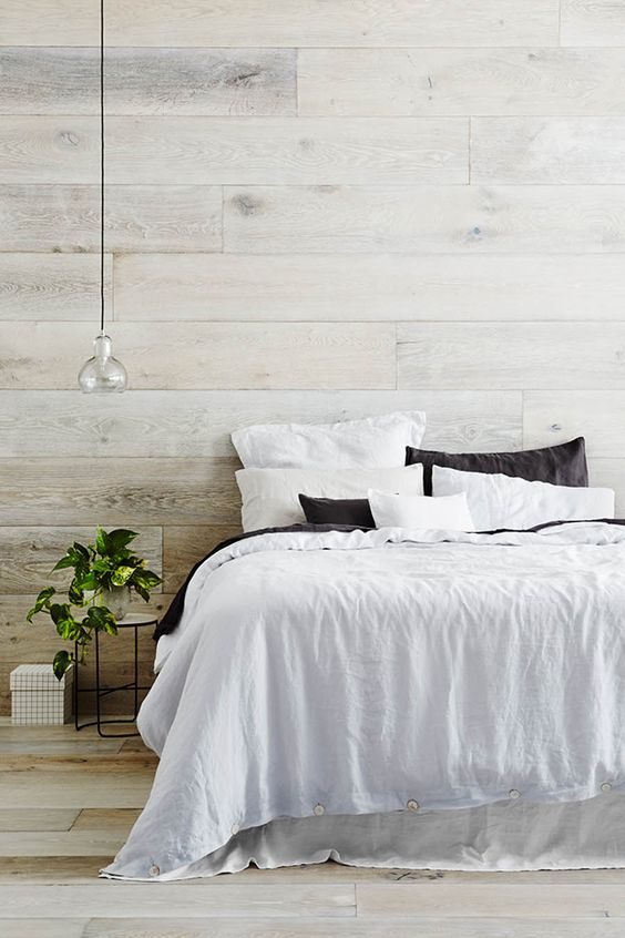 a cozy rustic bedroom with whitewashed walls and a floor - it's a great base for adding warmth and coziness
