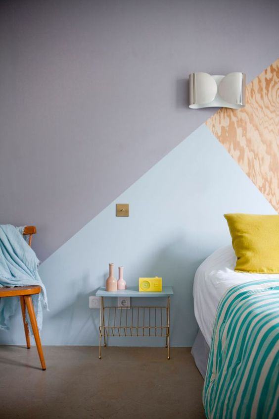 a geometric color block wall in grey, light blue and plywood for a chic and stylish bedroom