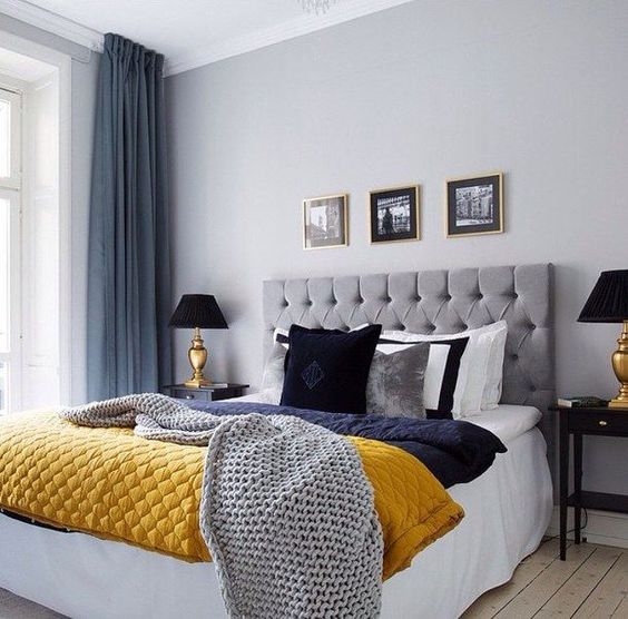 a grey and blue bedroom spruced up with a yellow blanket for a bright and cheerful look