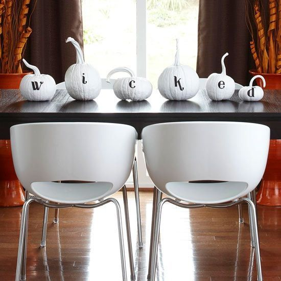 a minimalist pumpkin display in black and white instead of a usual table centerpiece is a cool idea