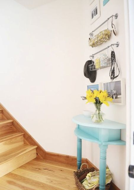 a stairwell landing is an awkward nook, it's decorated with a half table in blue and some hanging shelves