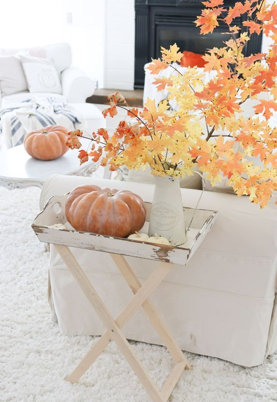 a vintage fall display with a little table filled with pumpkins and fall branches with leaves in a vase