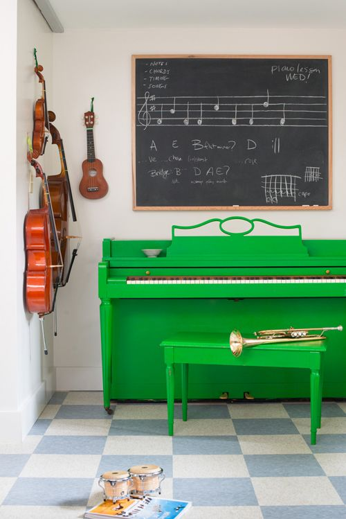 an emerald piano and stool, a chalkboard for making notes and other musical instruments for a music-loving person