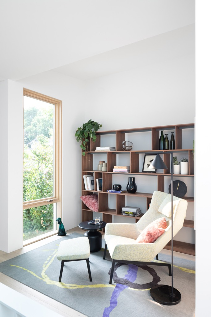 Comfy furniture is everywhere, here's a reading nook with a chair and a footrest plus a large storage unit