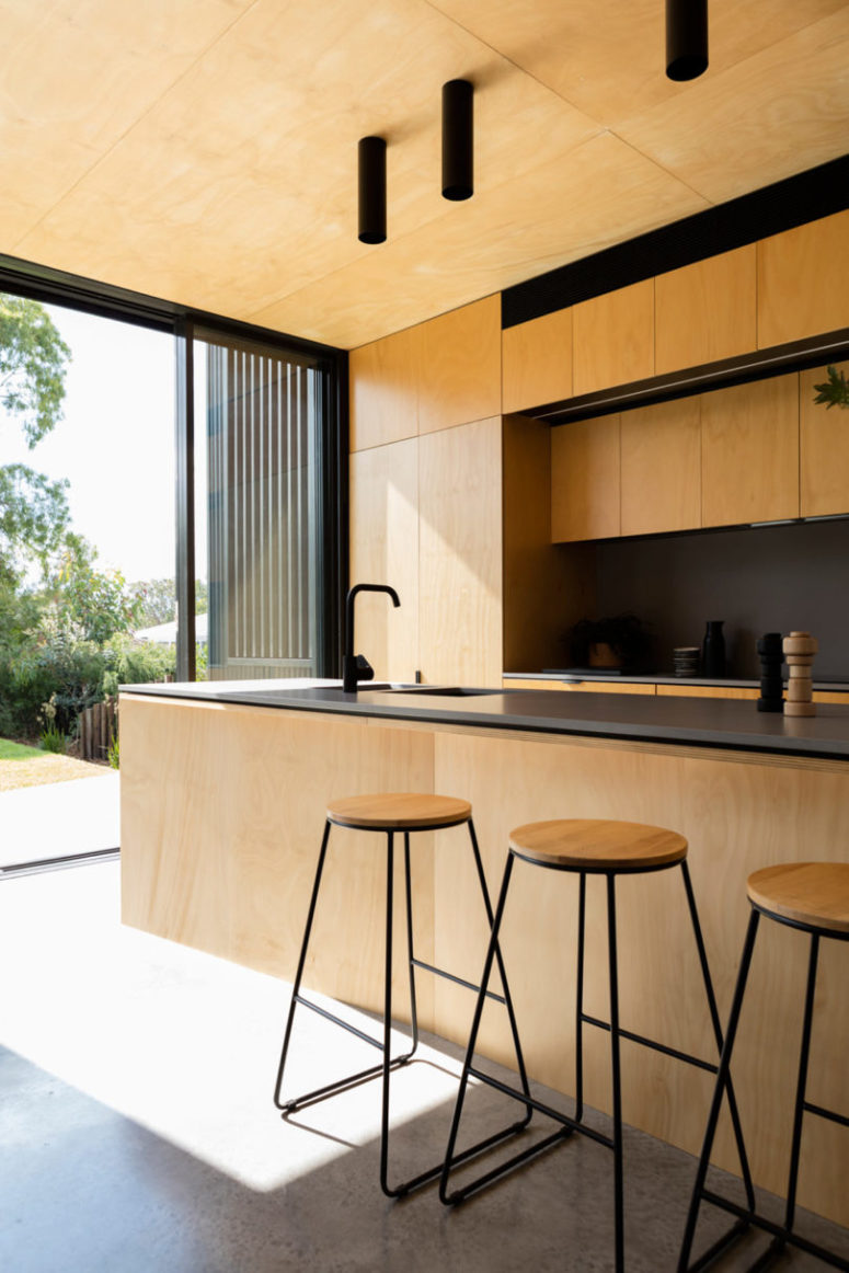 The contrast between light-colored plywood and blackened metal is a chic idea to go for