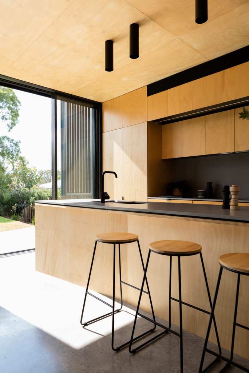 The contrast between light colored plywood and blackened metal is a chic idea to go for