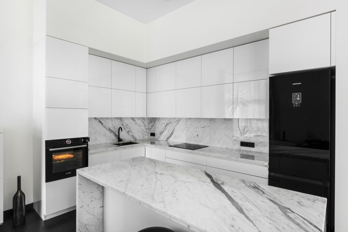 The kitchen is done in black and white with marble surfaces