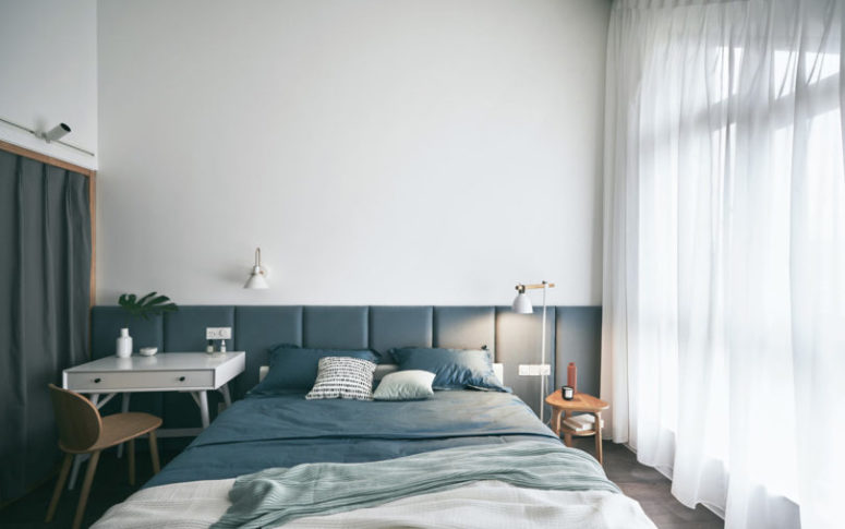 The master bedroom is a peaceful space in blue and white, with an upholstered headboard and a window that takes the whole wall