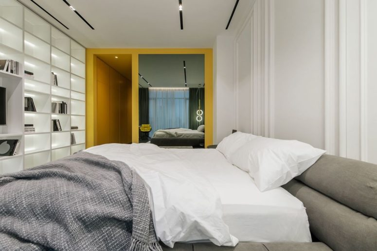 The second bedroom is all-white, with grey and yellow touches and there's an oversized storage wall unit
