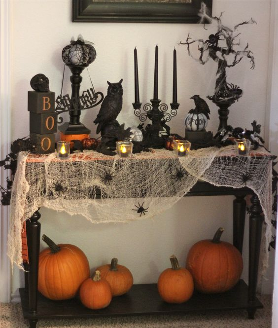 a Halloween console with spiderweb, fresh pumpkins, black candles and various figurines for a spooky feel