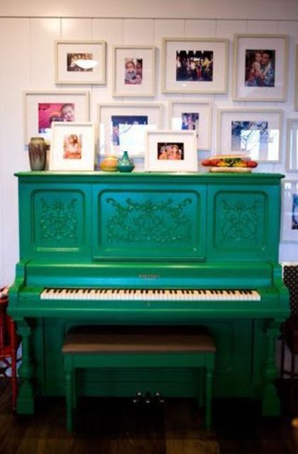 a bright emerald piano and stool and a display of family pics over the piano