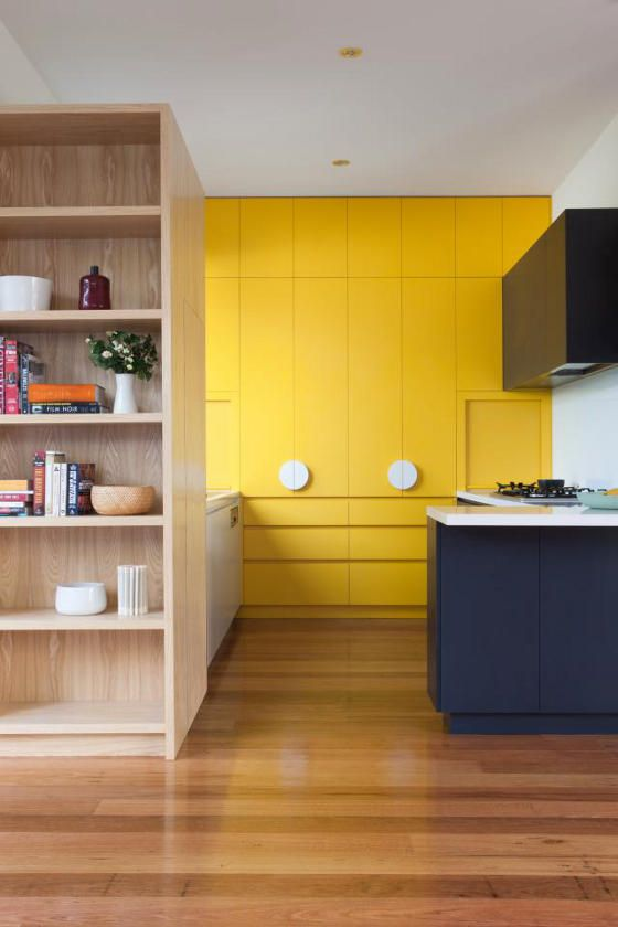 a chic contemporary kitchen in navy and sunny yellow with sleekdesign and white touches