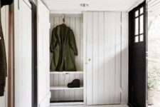 10 a cozy and simple entryway with whitewashed wood plank walls, ceiling and storage furniture