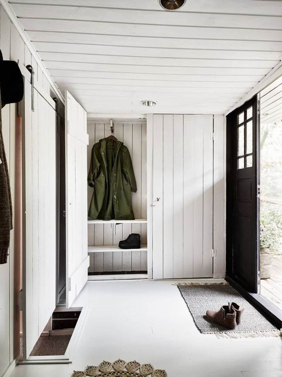 a cozy and simple entryway with whitewashed wood plank walls, ceiling and storage furniture