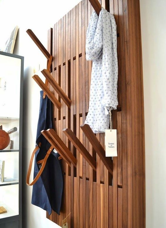 a creative wall-mounted clothes rack with wooden sticks that can be pulled out when needed and then hidden again