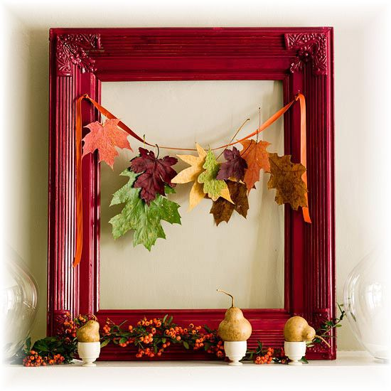 a cute and bold fall display with a red frame, a fall leaf garland and pears on egg stands