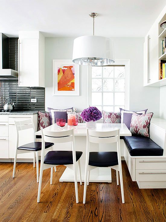 a little lively nook with a corner seating and a square table plus chairs, colorful pillows for a vivacious feel