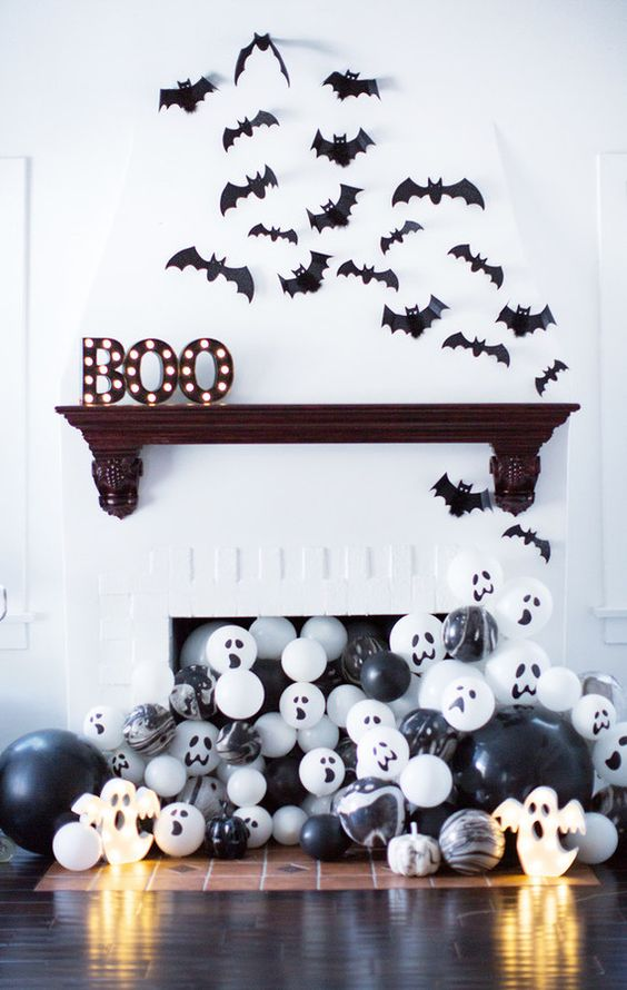 a modern Halloween mantel with marquee letters, bats and lots of black and white balloons in the fireplace