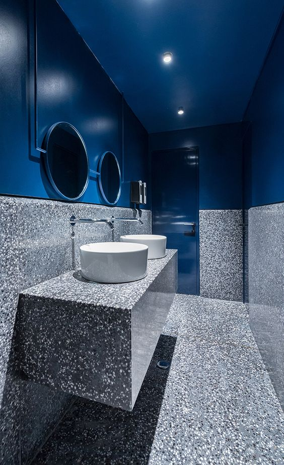 a powder toom in blue and grey stone features not only a color block effect but also a material juxtaposition