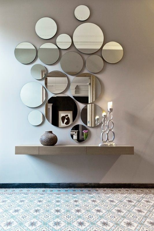 an arrangement of round mirrors of various sizes and a floating vanity for an ethereal look
