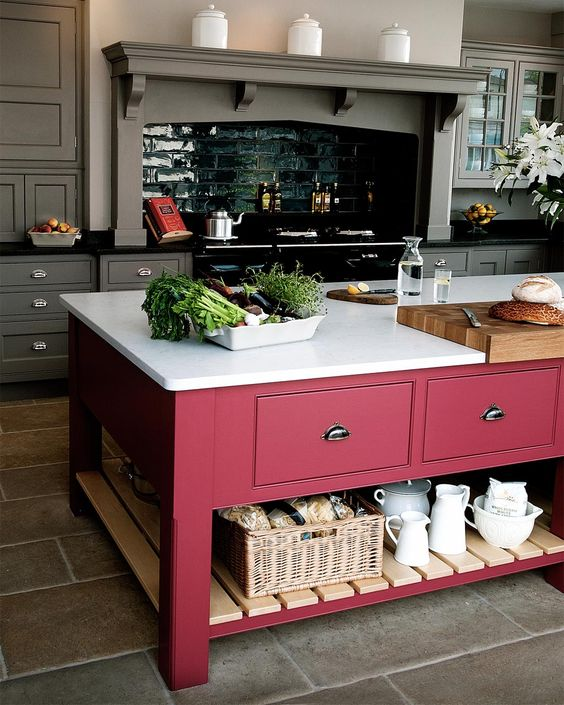 a color block effect is achieved in this grey kitchen with a bright pink kitchen island with a white countertop