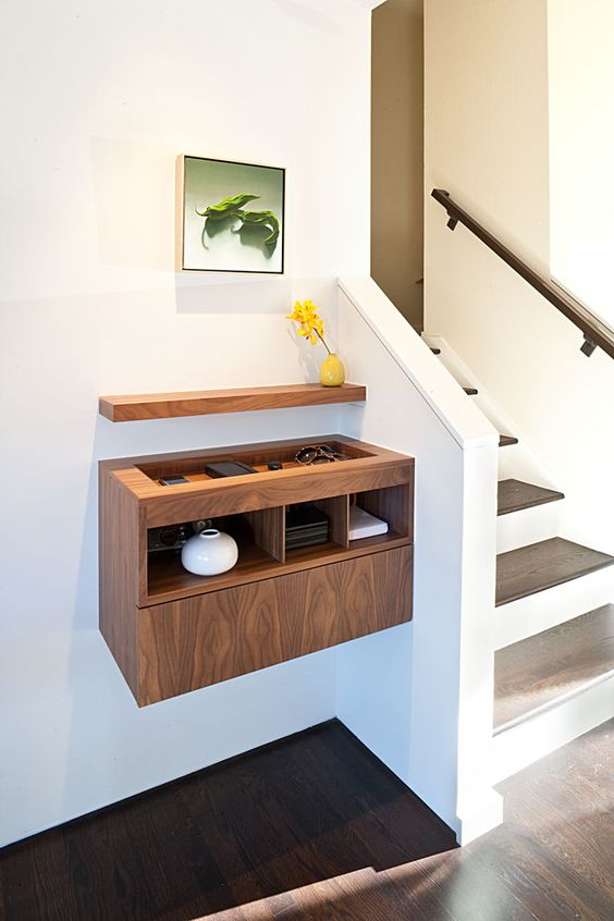 a contemporary plywood floating console with a sunken tabletop and a small shelf over the console